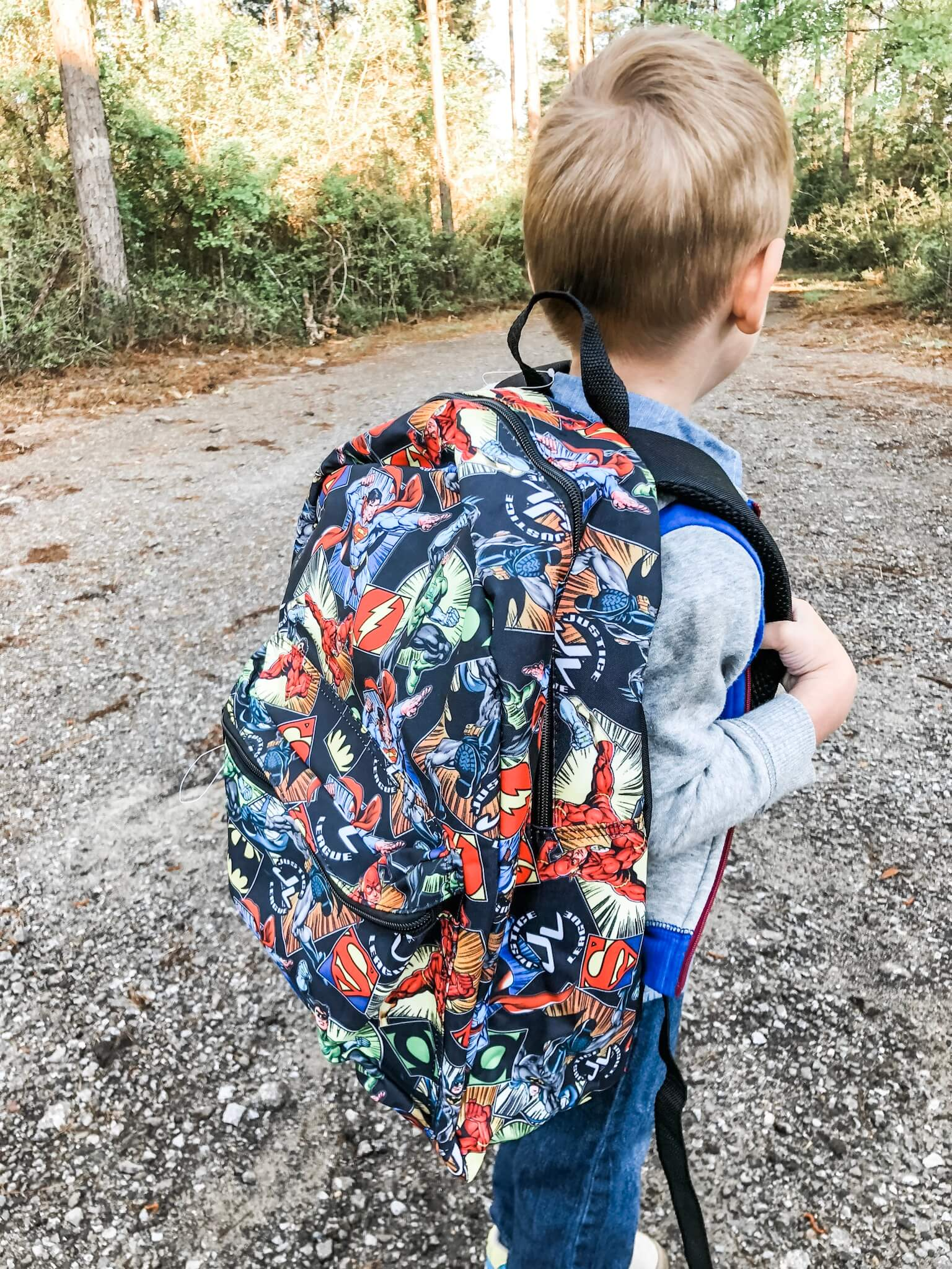 Little Boy wearing a backpack facing the woods. First Week of School picture.