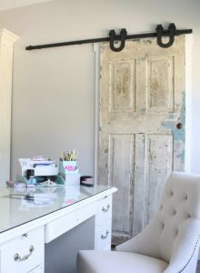 A home office with a white desk and white chair and a barn door