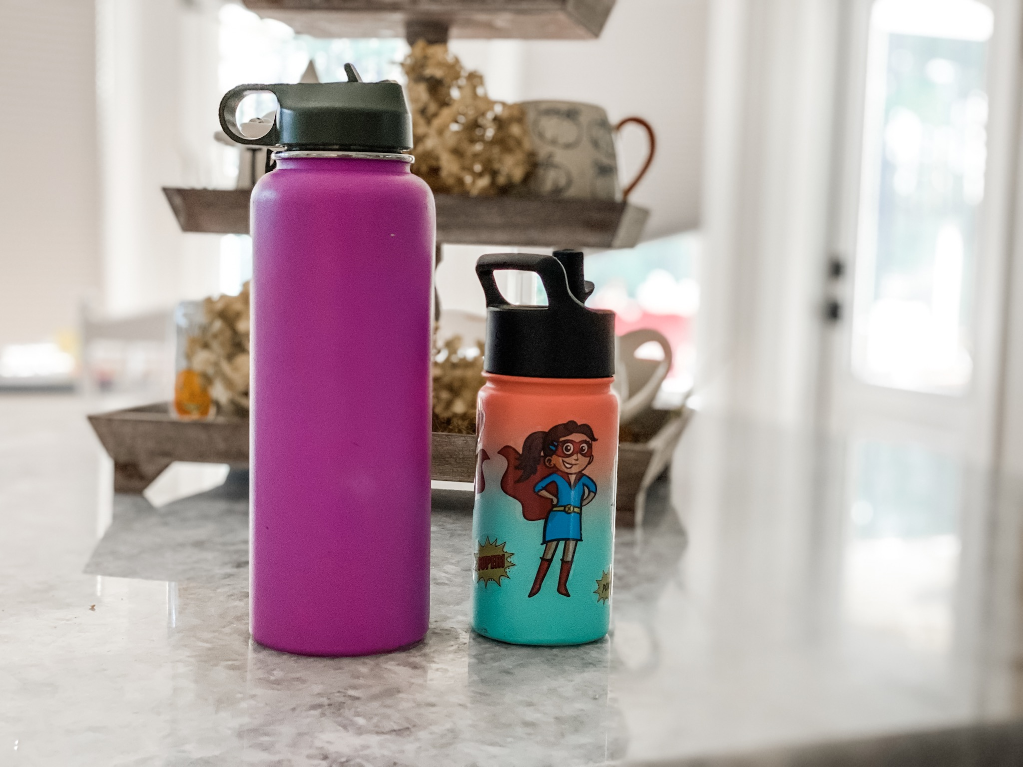 A large water bottle beside a child water bottle on a counter.